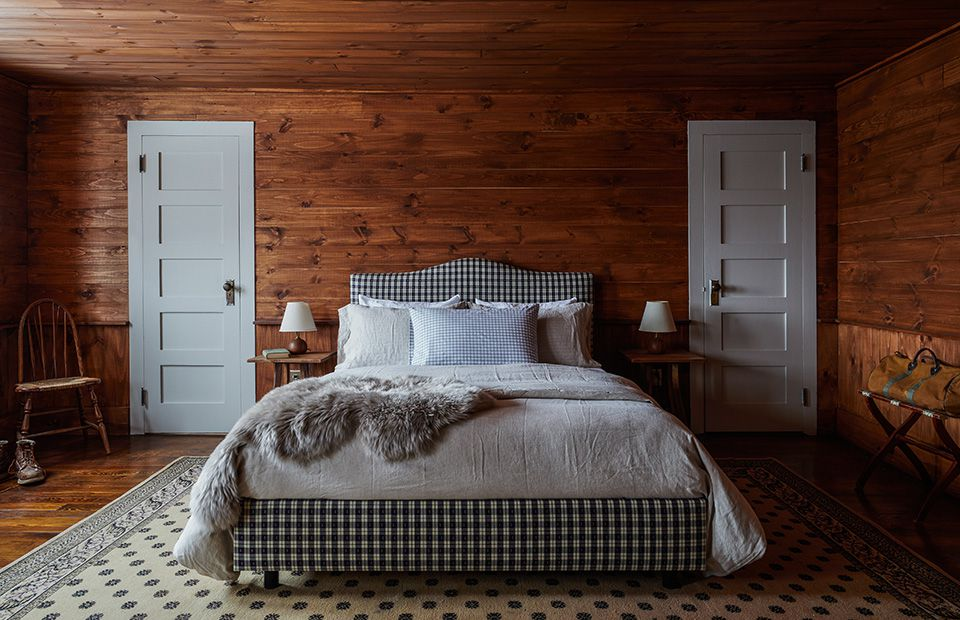 A wood-paneled bedroom with a plaid bed