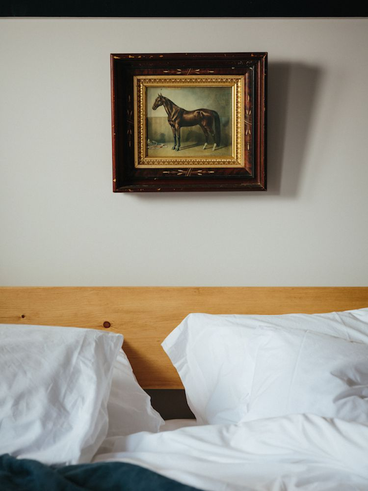 A bedroom with a small painting of a horse