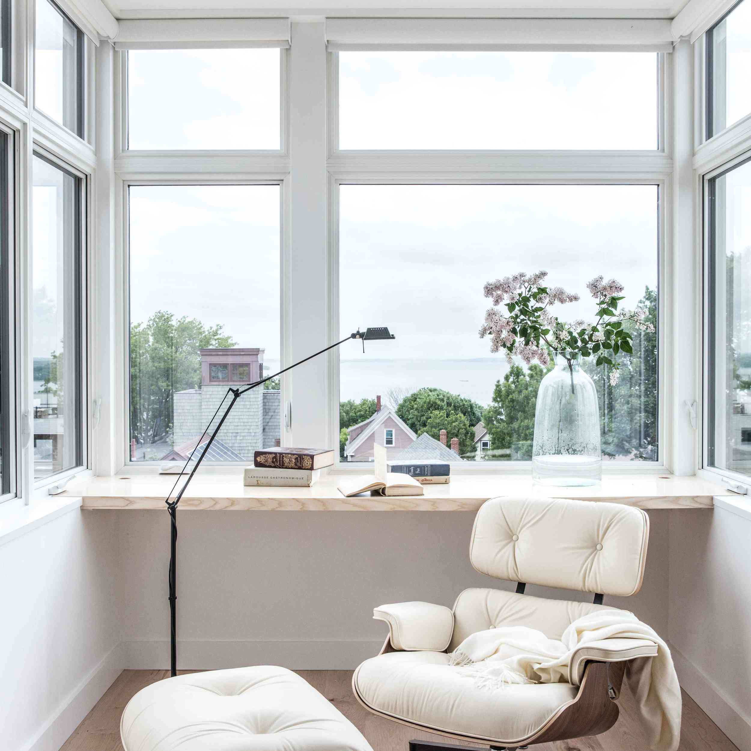 A window-lined home office outfitted with a white Eames lounge chair