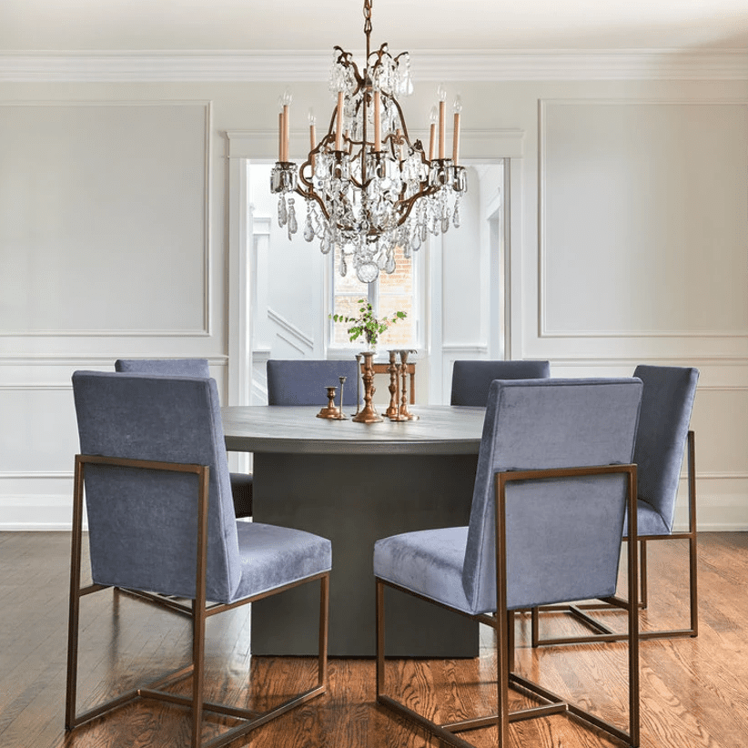 A circular dining room table surrounded by plush blue chairs