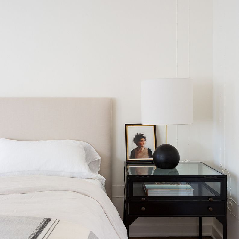 Clean and simple bedroom with neutral bed and nightstand with lamp