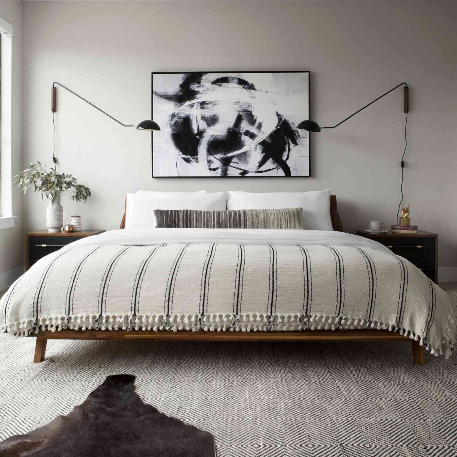 A modern bedroom with two massive modern swing-arm sconces