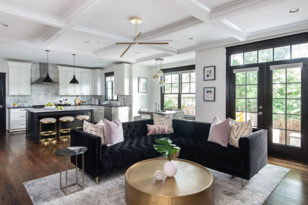 Open-concept living space with black velvet sofa and purple throw pillows