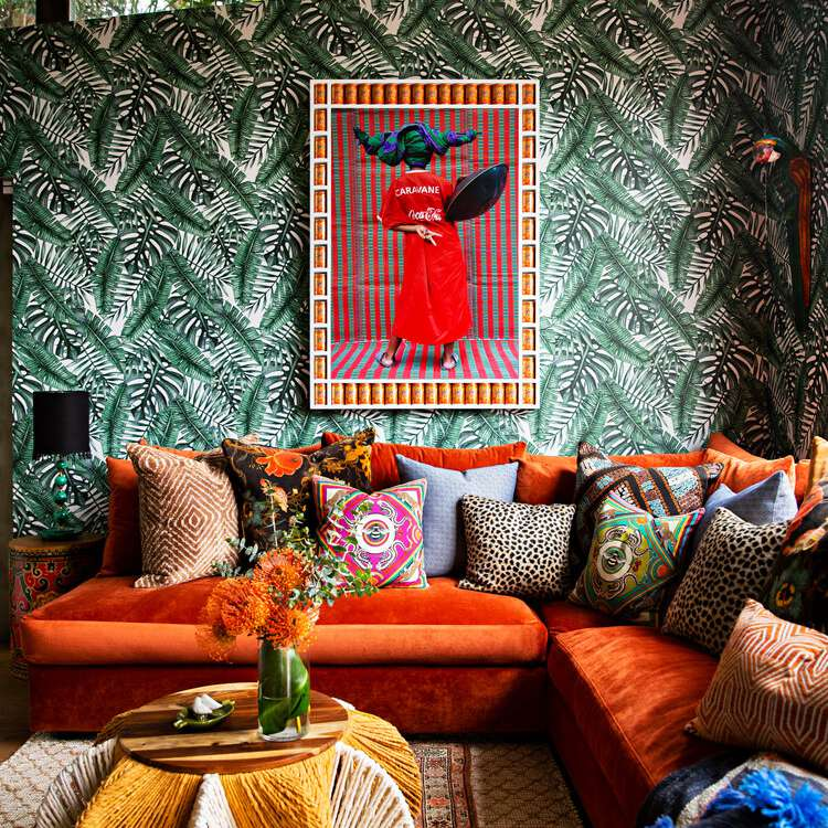 Eclectic bedroom with printed wallpaper and leopard pillows.