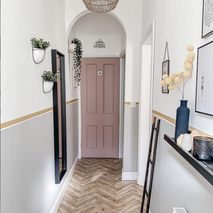entryway with pink front door, mirror, floating shelf and floating plants