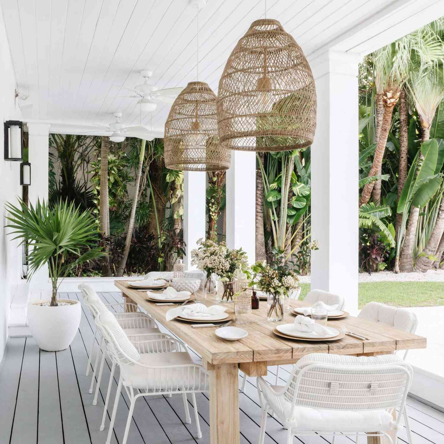 An outdoor dining room with white chairs and two woven pendant lights