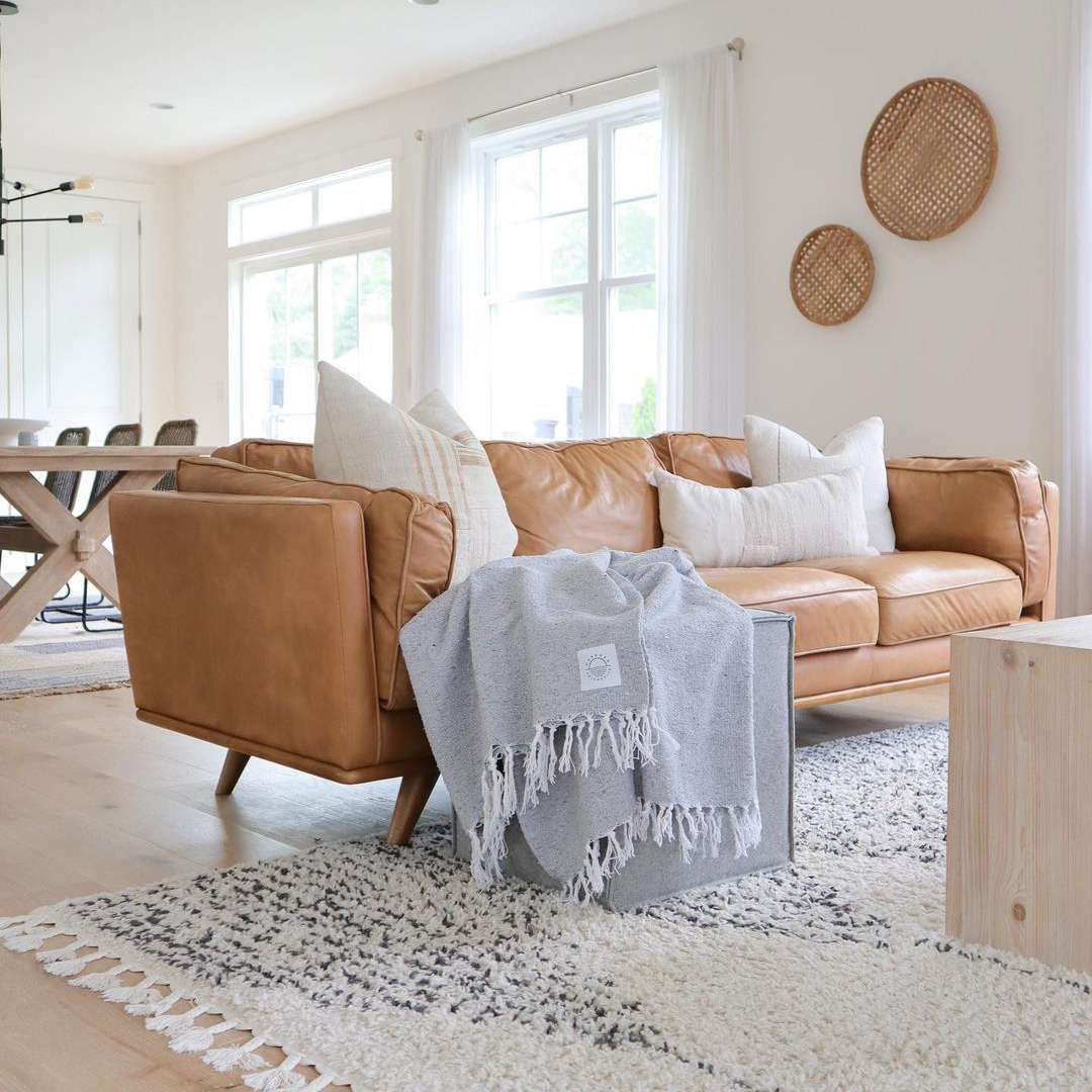 Large leather sofa with throw pillows and blanket.
