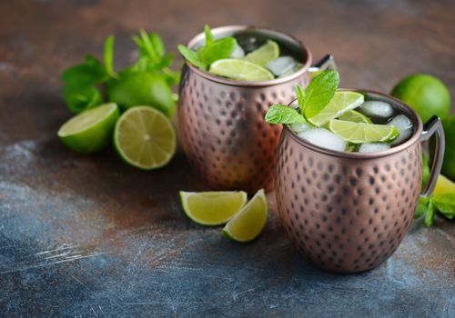 Moscow Mules in two copper mugs, garnished with lime wedges and mint.