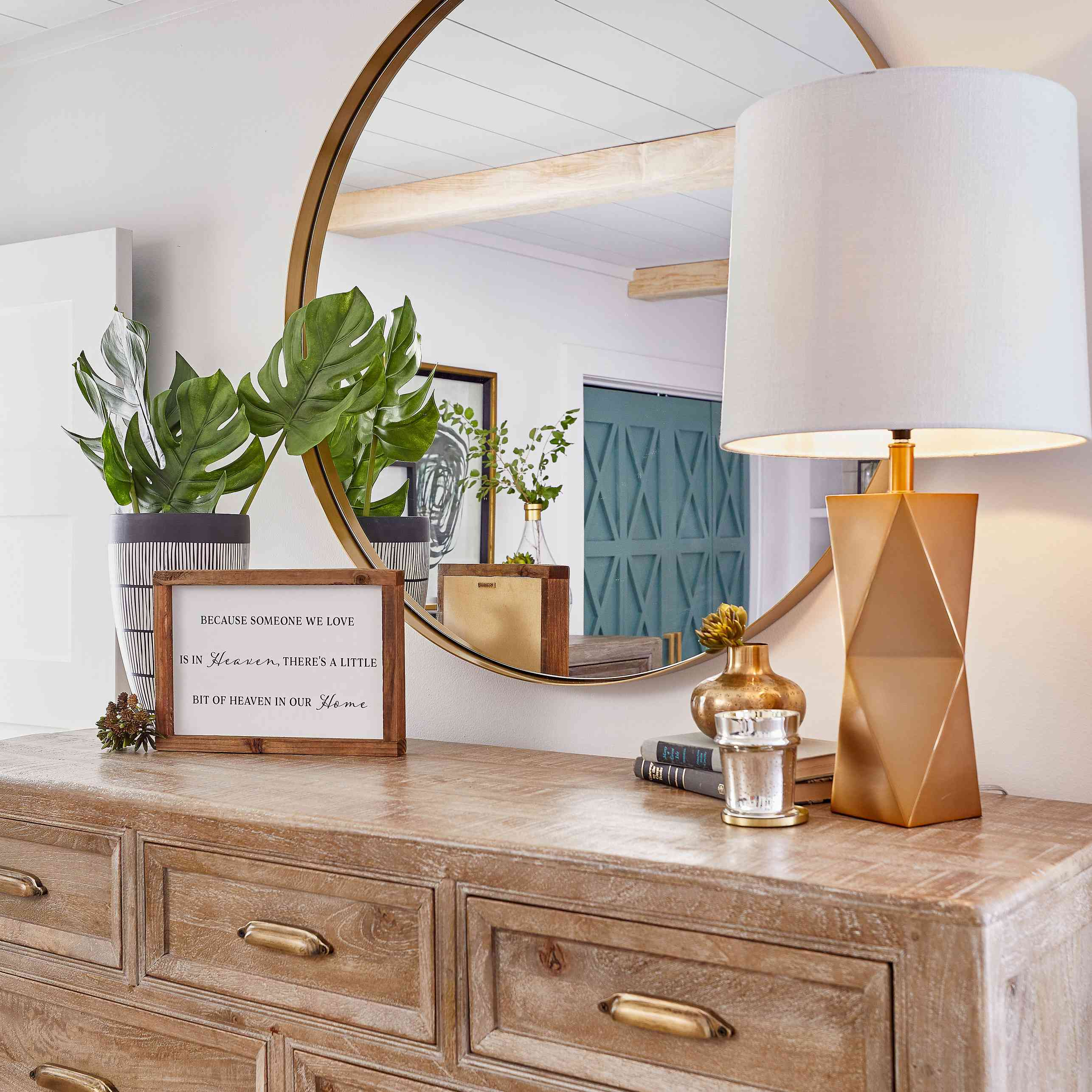 Dresser with gold lamp and rustic decor.