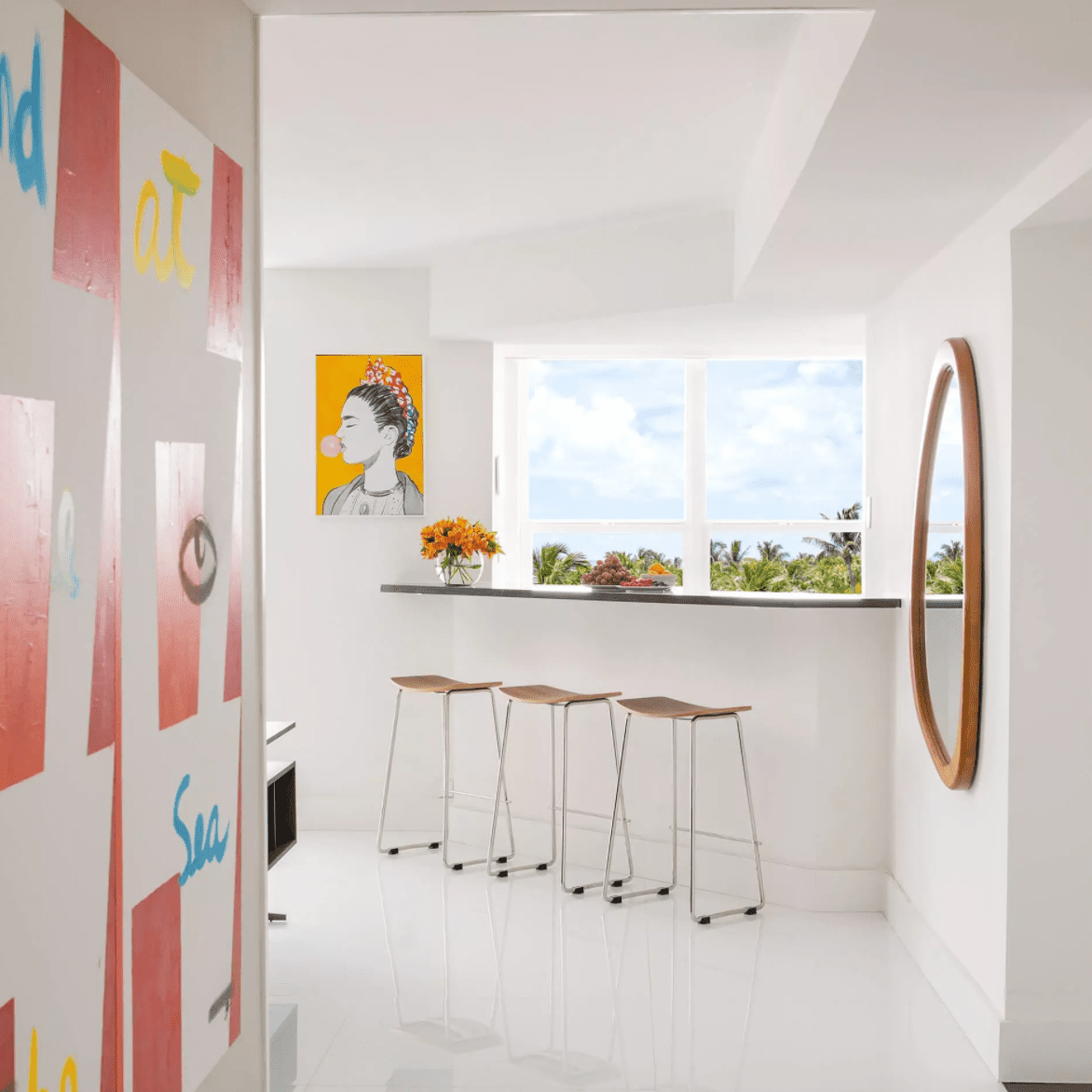 A hallway leading into an all-white kitchen, with several walls lined with modern art