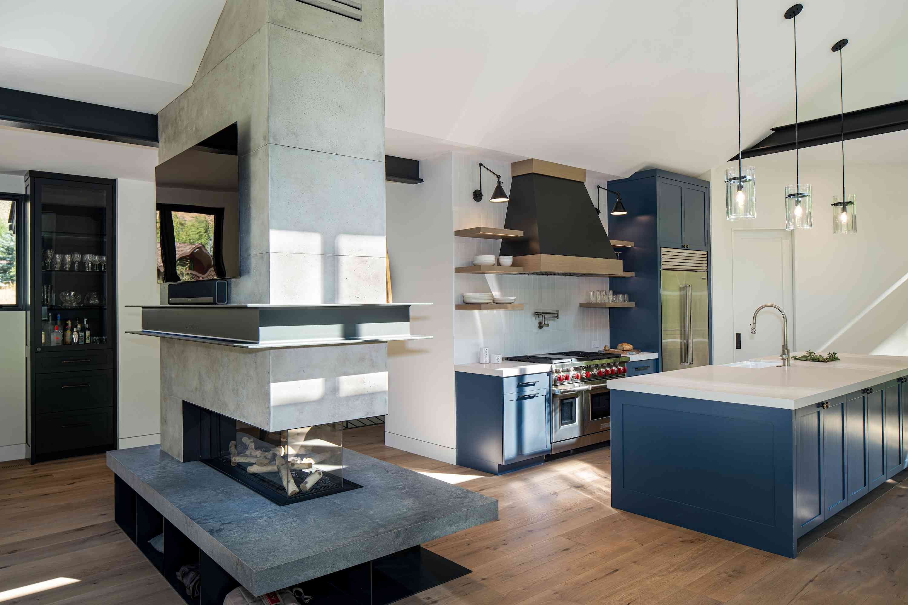 After shot of sleek modern kitchen with open fireplace.