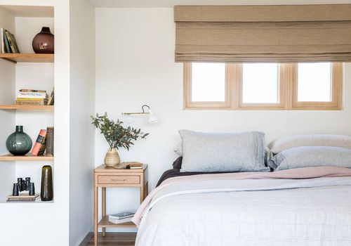 Soft neutral bedroom with pieces of decor on shelf.