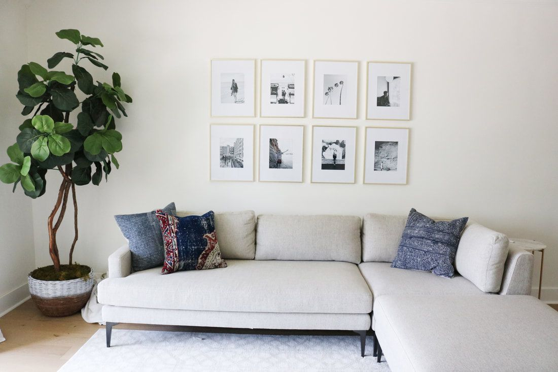 Neutral sectional and black and white gallery wall hanging above.