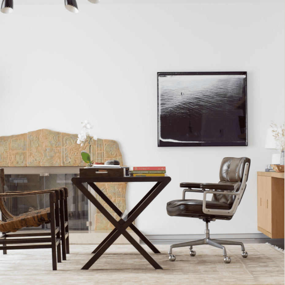 A home office furnished with a desk and three chairs—all of which have been placed in the center of the room