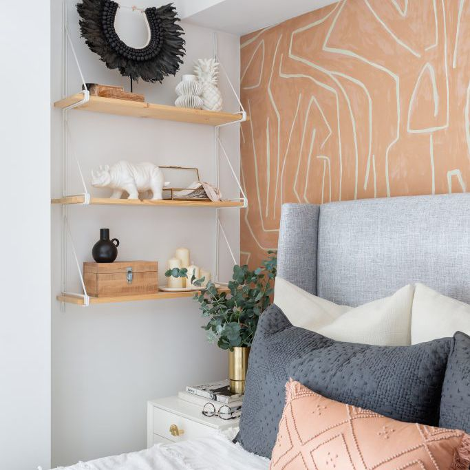 A bedroom with orange printed wallpaper