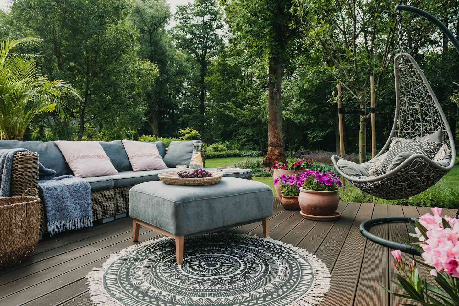 Outdoor seating area with couch, ottoman, hanging chair, and rug.