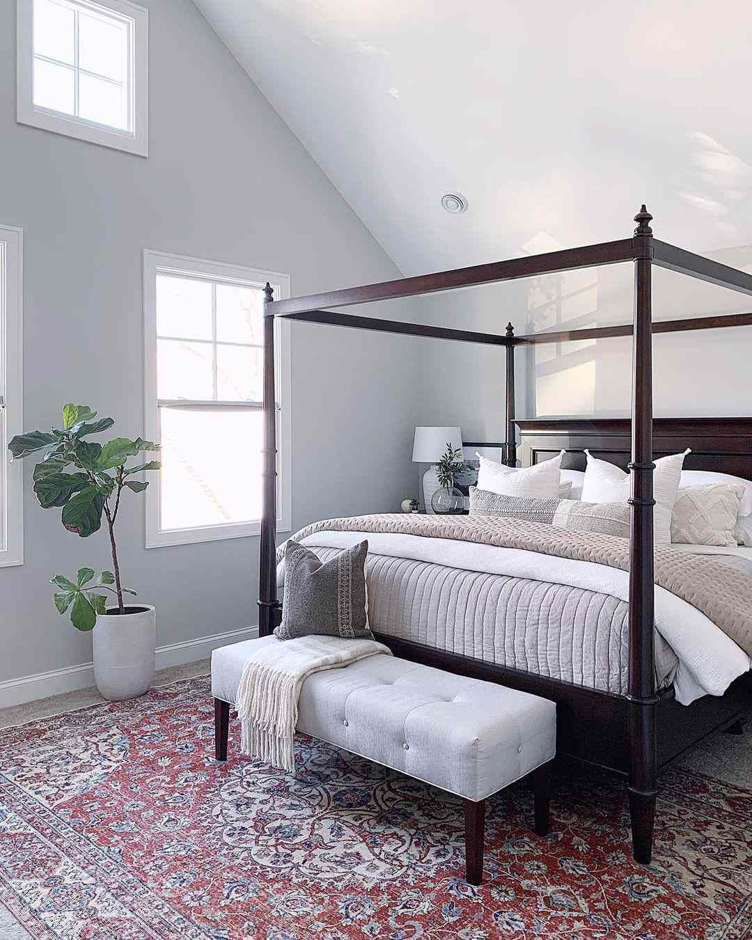 Bedroom with many windows and canopy bedframe.