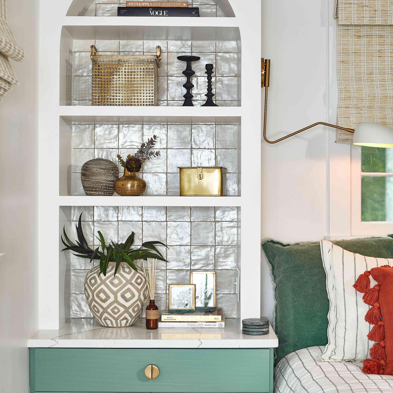 Built in bookshelf with glossy tile backsplash.