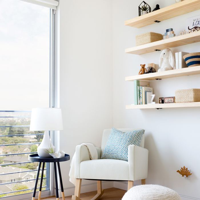 nursery with rocking chair and floating wall shelves