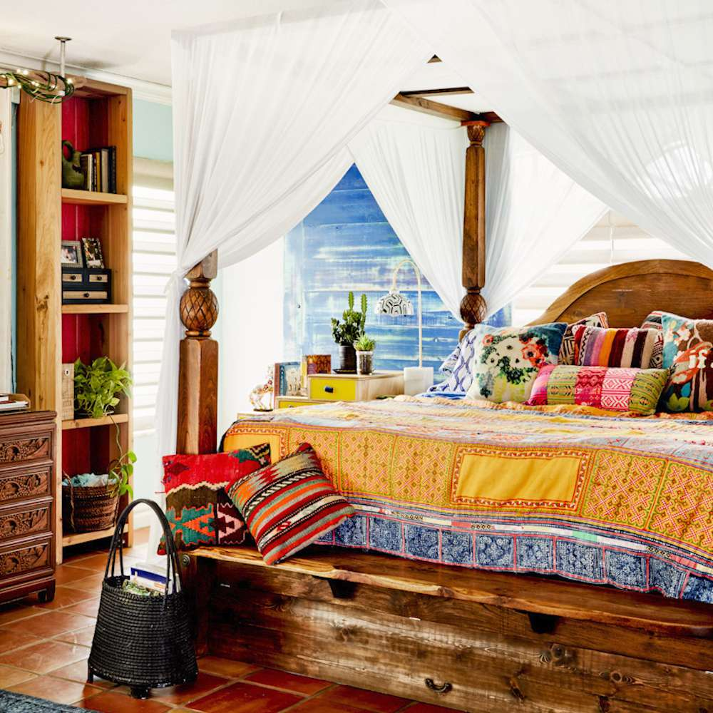 A maximalist bedroom with a white linen canopy