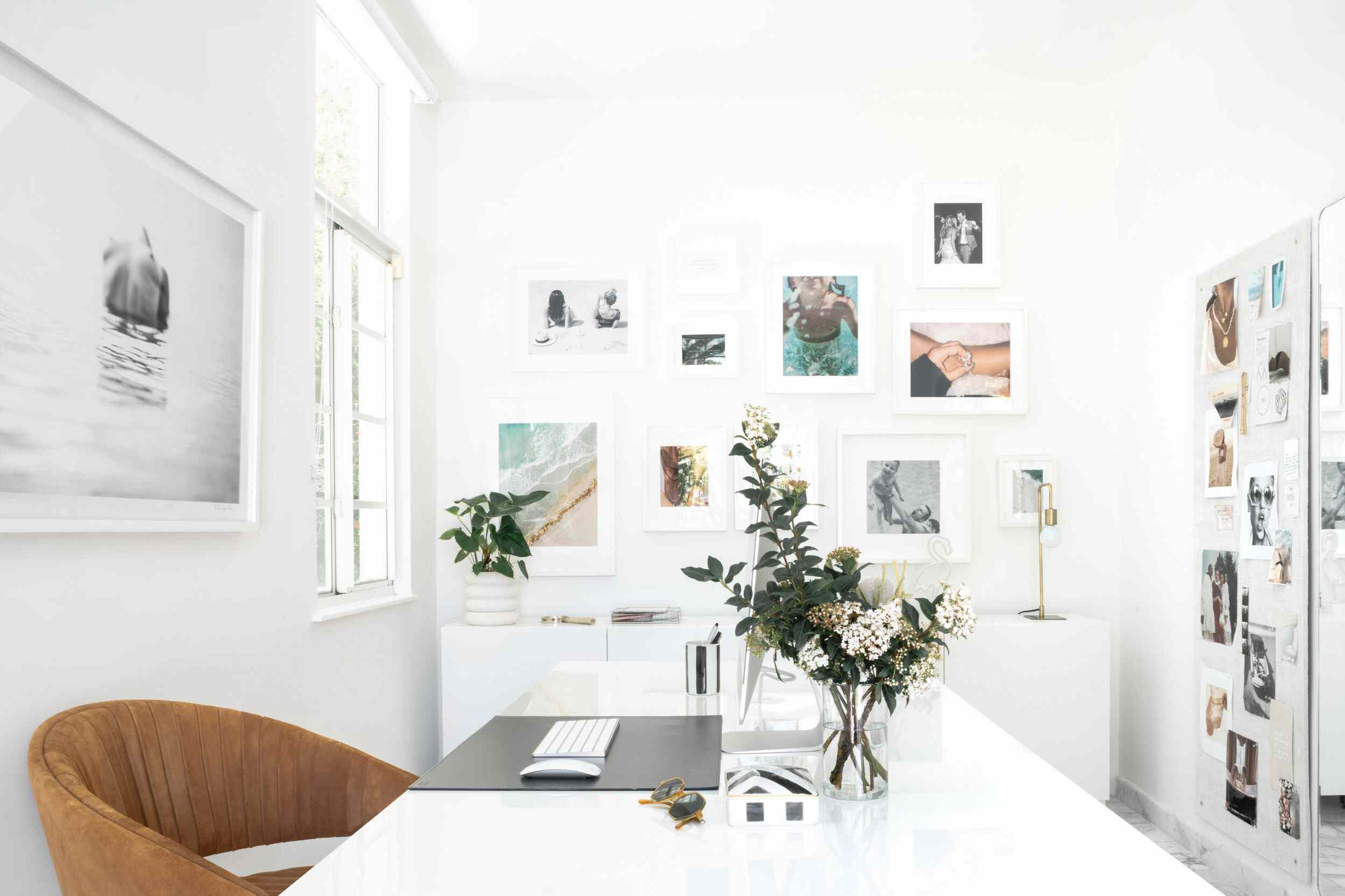A white home office decorated with gray and blue photographs and a striking silver desktop monitor
