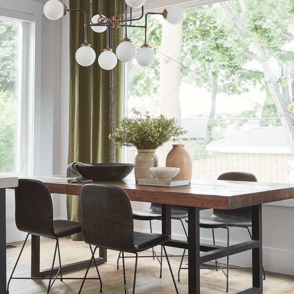 A modern dining room with a bold lighting fixture