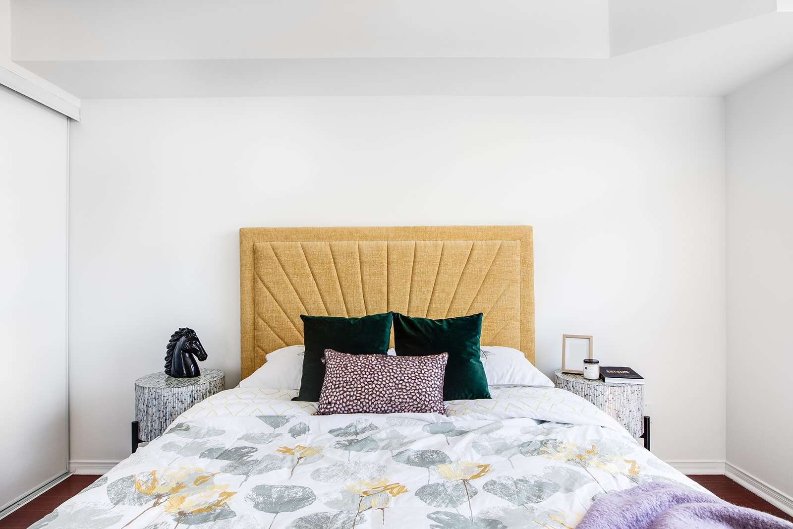 Bedroom with bright yellow headboard and purple accents