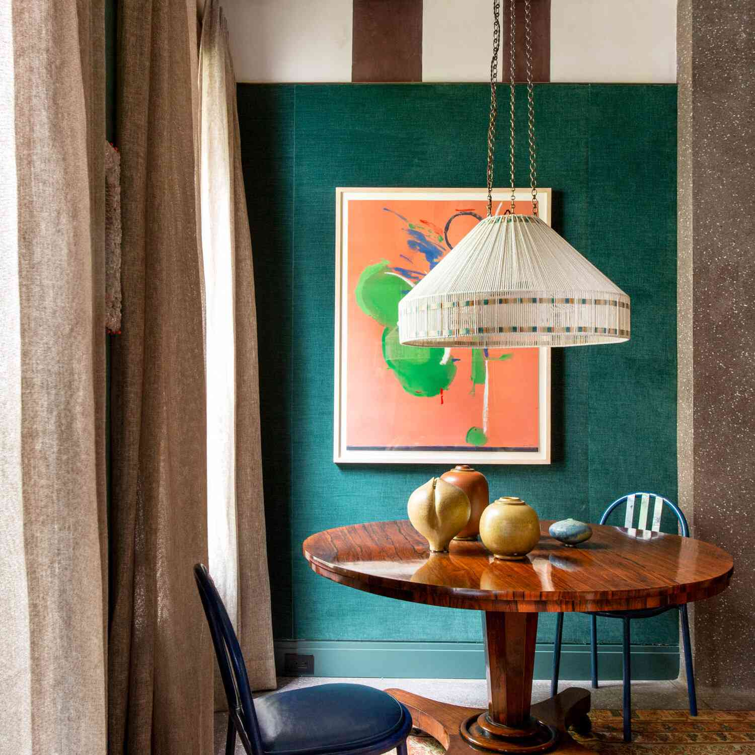 A dining nook with jade green walls, a salmon-colored rug, and matching salmon-colored art