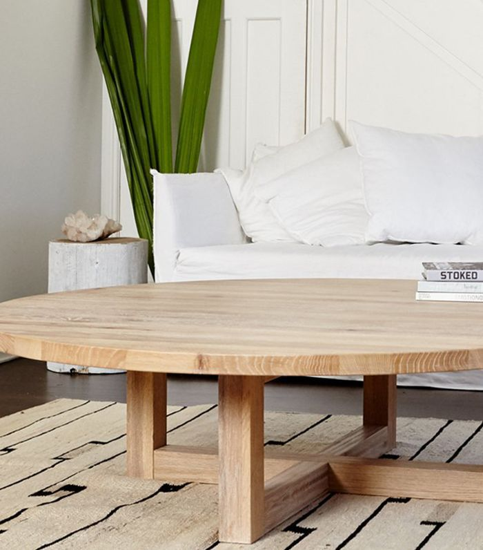 A round, minimalist, wooden coffee table on a tribal rug.