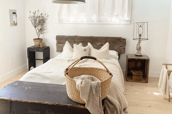 A rustic farmhouse bedroom with an antique bed frame