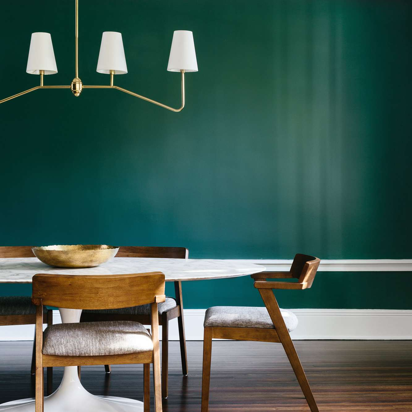 A dark green room with sculptural furniture