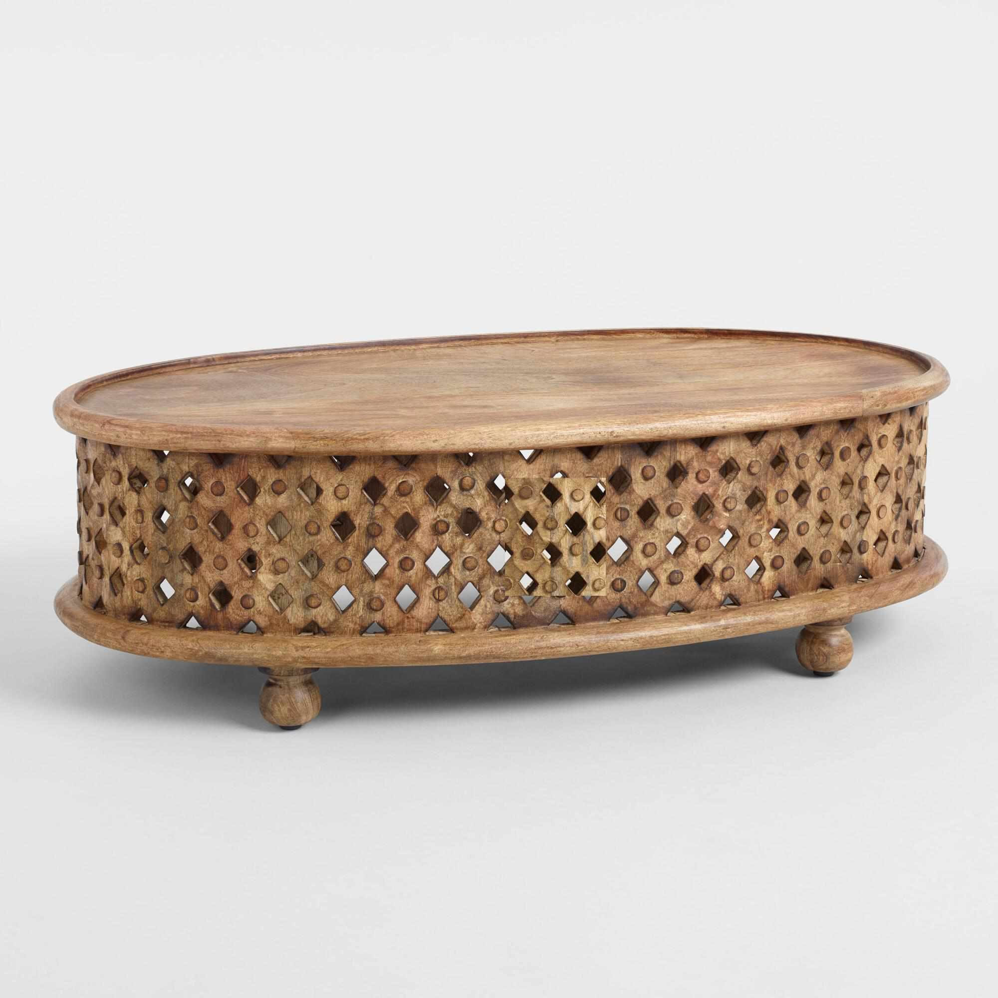 An oval carved-wood coffee table with bun feet.