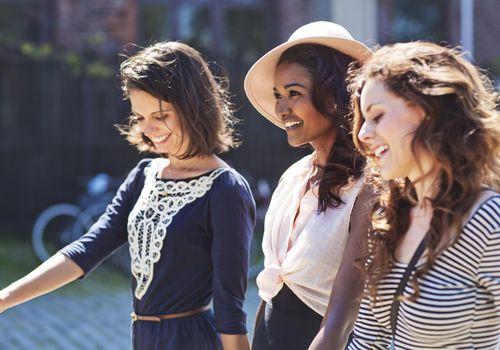 Tres elegantes amigas caminando juntos