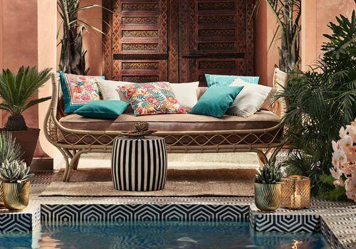 Muebles de exterior junto a la piscina con soportes para plantas de oro.