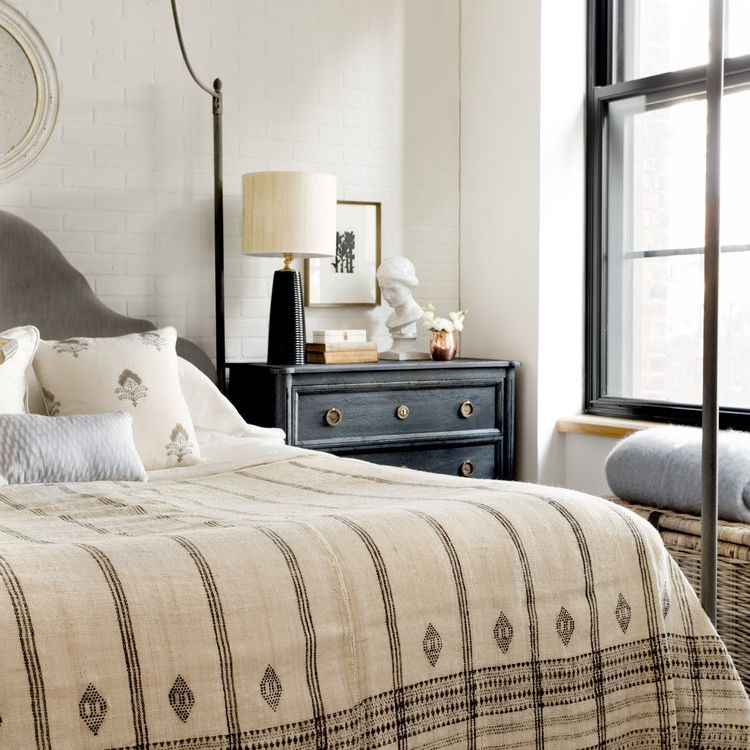 A bedroom with a beige bedspread and a navy nighstand