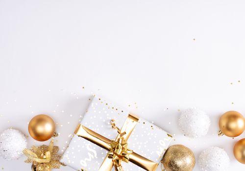 Regalo envuelto rodeado de adornos de oro y blanco.