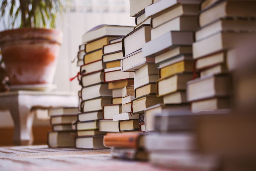 Piles of books stacked on a carpet