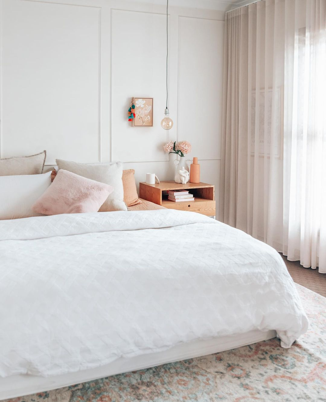 Neutral bedroom with pink and peach accents.