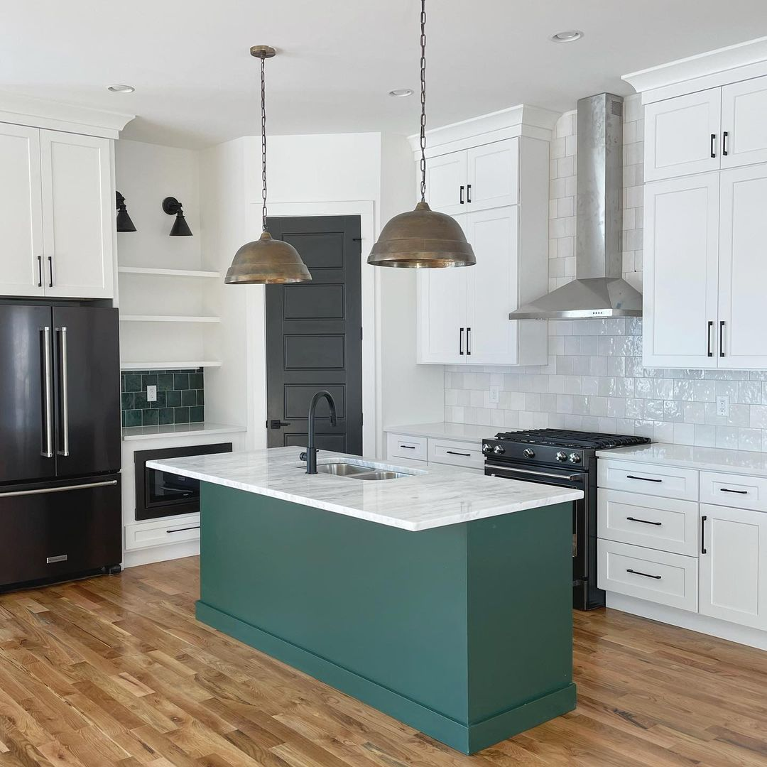 Kitchen with white cabinets and wood laminate flooring.