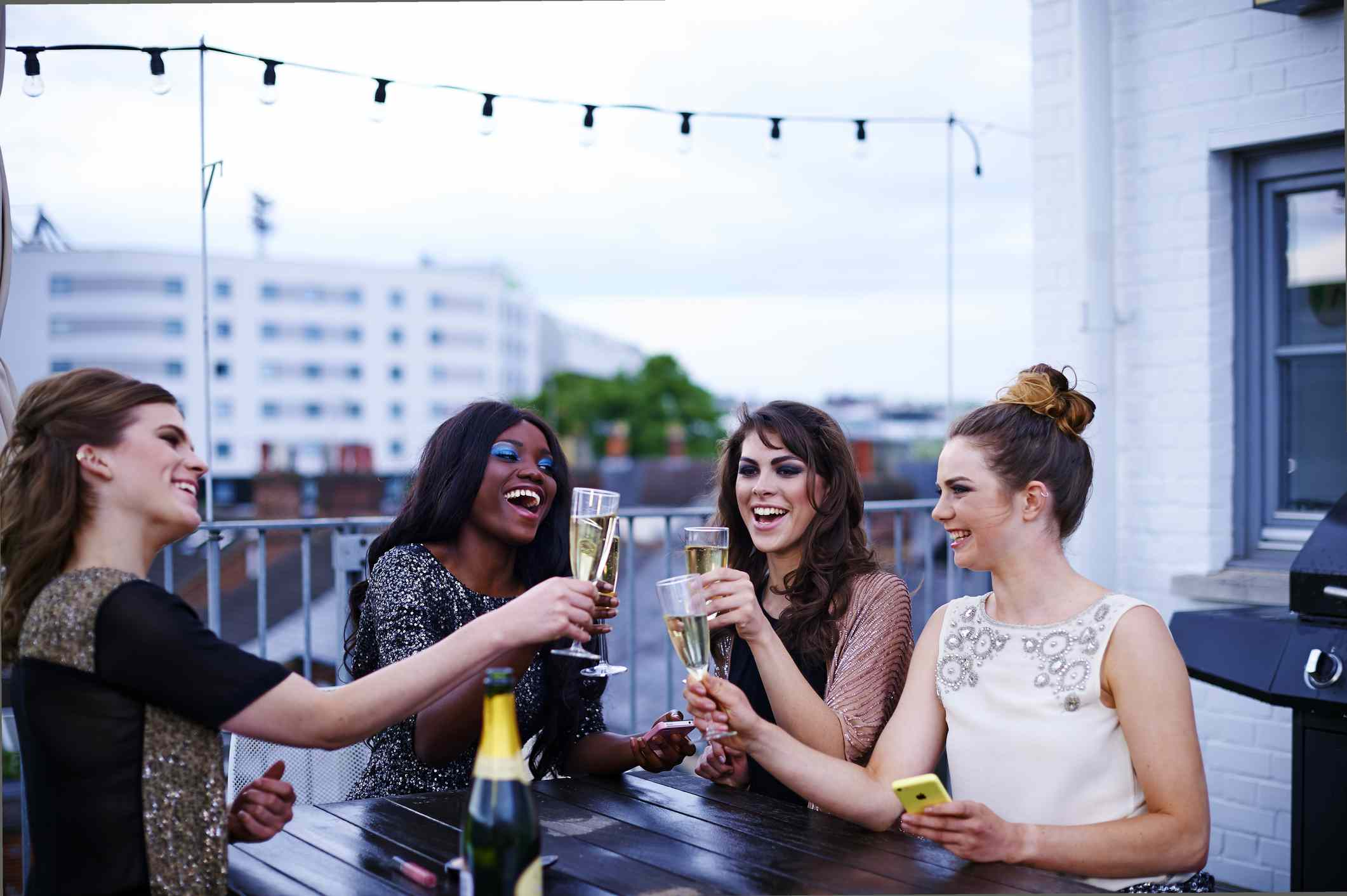 Group of women clink Champagne glasses on a rooftop