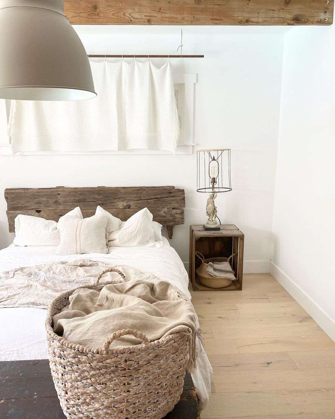 Rustic neutral bedroom with exposed wooden beam.