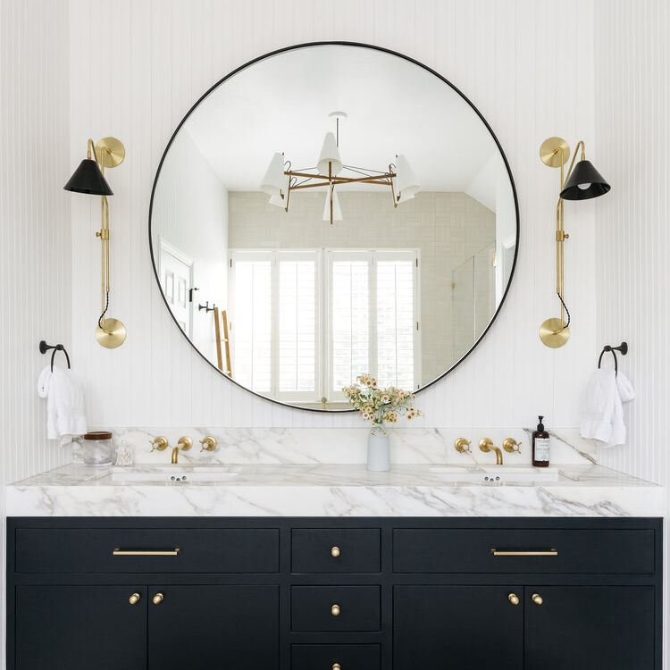 A double vanity with a large circular mirror