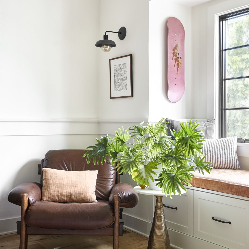 Skateboard hung as wall decor above a brown leather chair