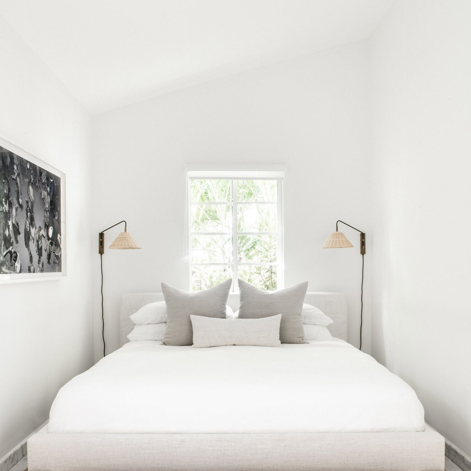 A minimalist bedroom with two woven sconces