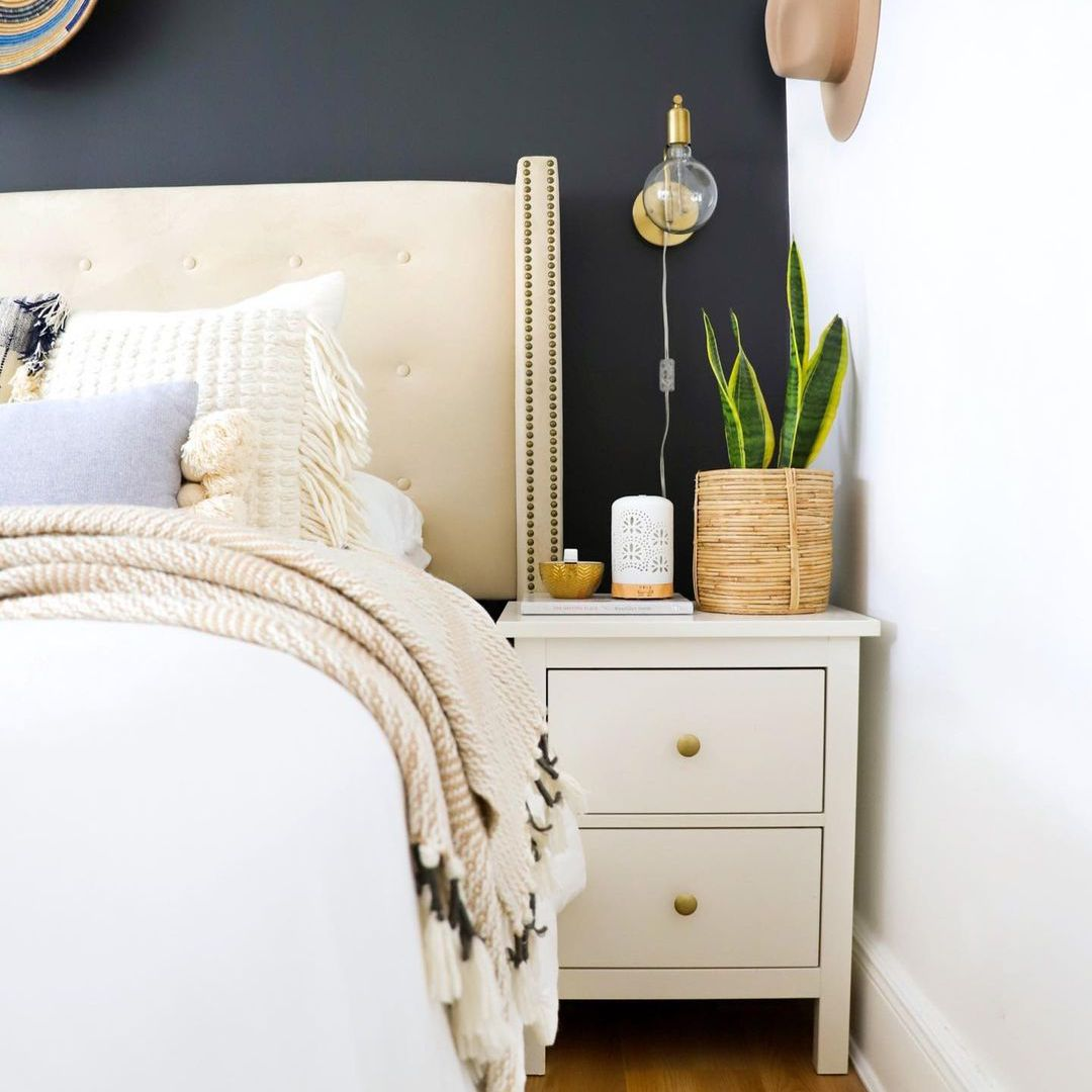 Neutral boho bedroom with snake plant on nightstand.
