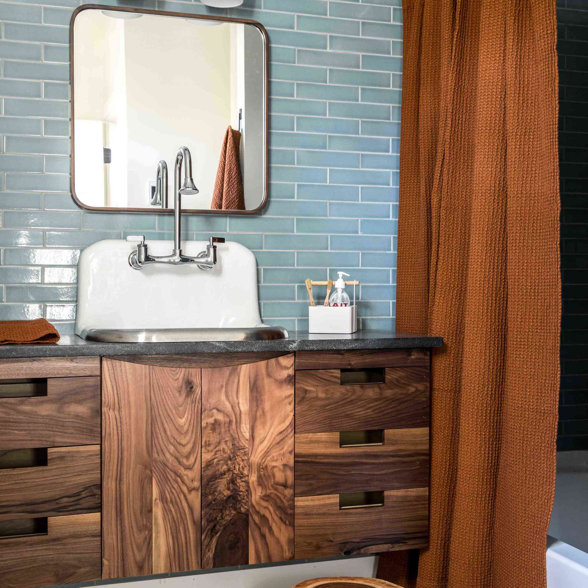 A tile-lined bathroom with a white sink that has a built-in backsplash