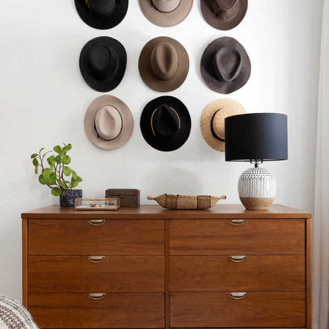 A bedroom wall decorated with a console table and nine hats mounted on the wall
