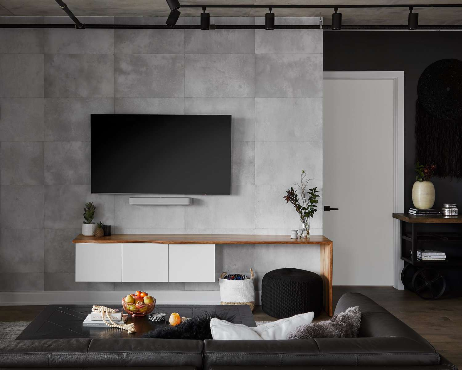 A living room with cement ceilings and industrial ceiling lighting