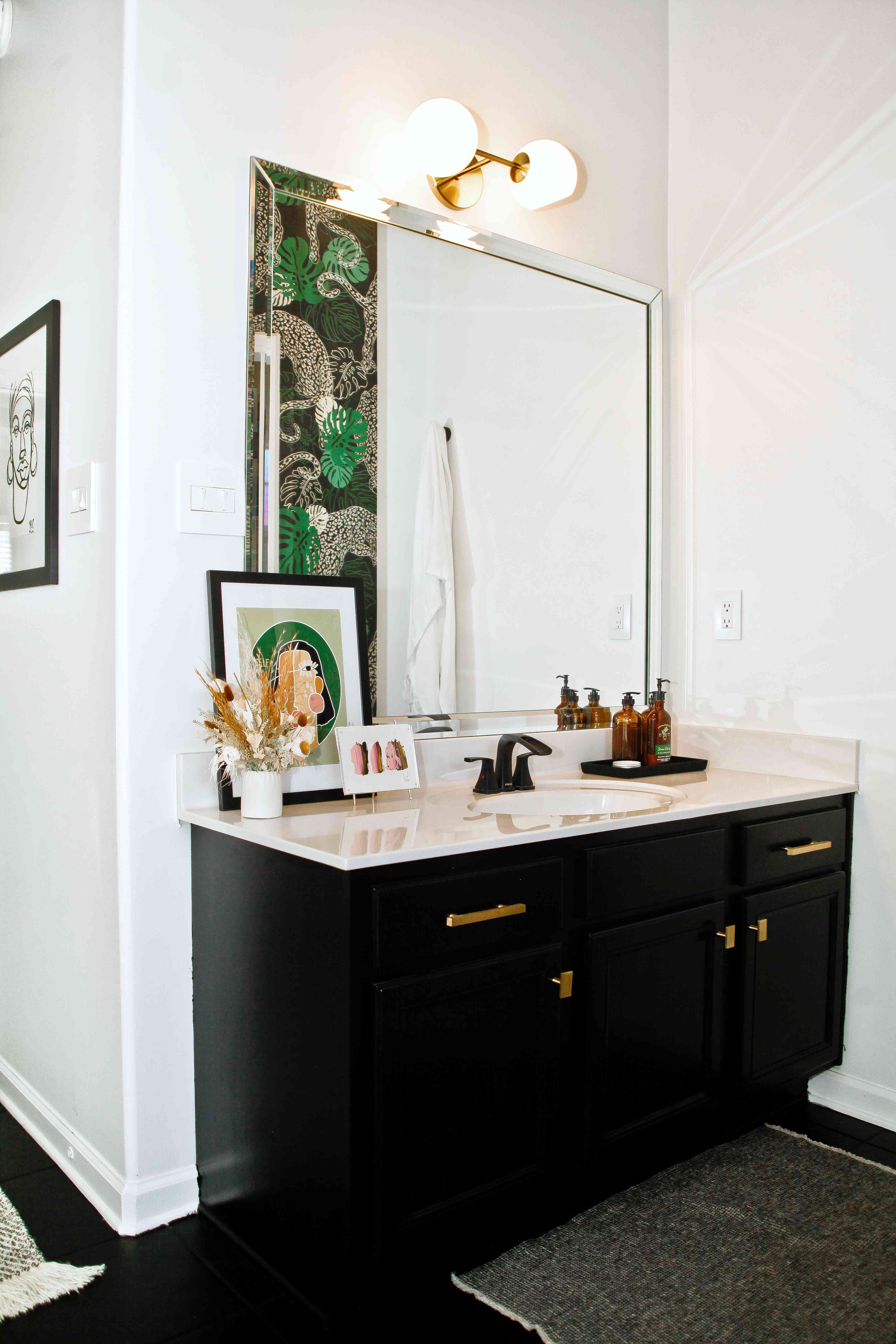 one room i'll never forget - laquita tate vanity with sconce and leaning artwork