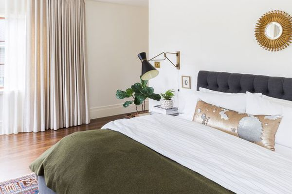 a neutral bedroom with olive green bedding